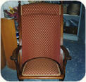 Folding campaign chair with separate cushion and rust red Damask upholstery.  Pincushion seat and Back reupholstered with matching fabric. Padded backrest. Repaired wood filled and polished.